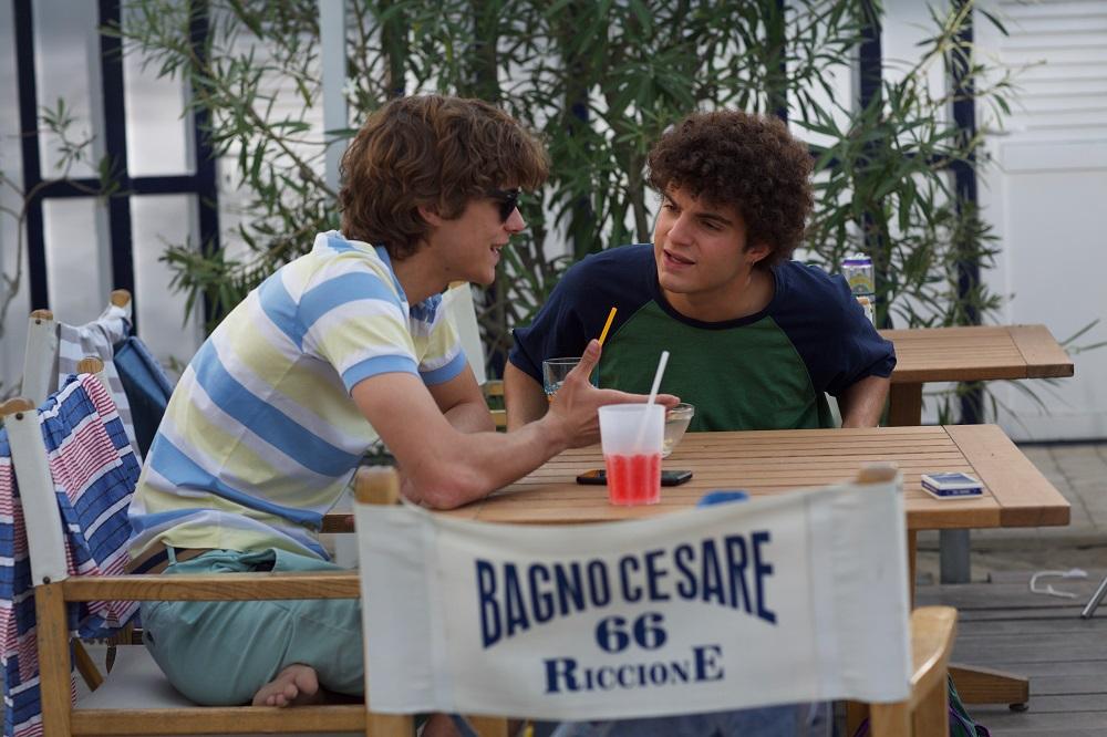 Lorenzo Zurzolo (Vincenzo) e Davide Calgaro (Furio) in una scena di Sotto il sole di Riccione. Sono entrambi seduti ad un tavolino del lido e stanno parlando.